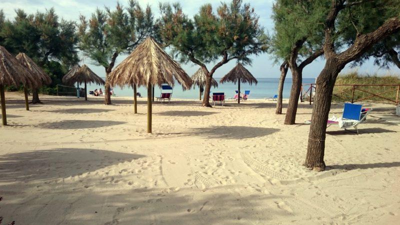 rieten parasolletjes op het strand van cisternino