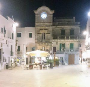 historische klok en terrasje op dorpsplein van Cisternino , een van de vele dorpjes Puglia