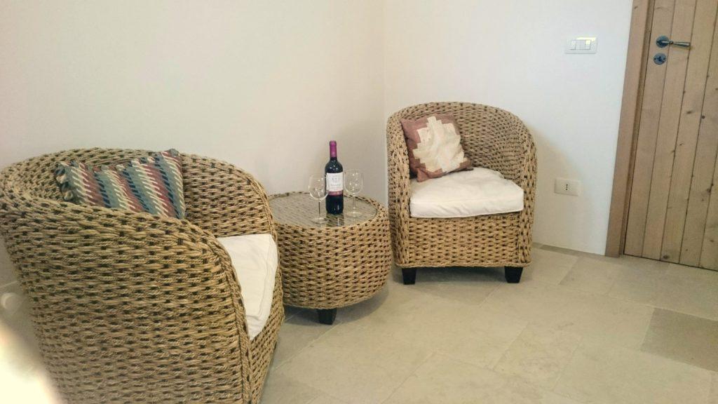 Flora lounge met bananenrieten stoeltjes tafel met flesje wijn en wijnglazen