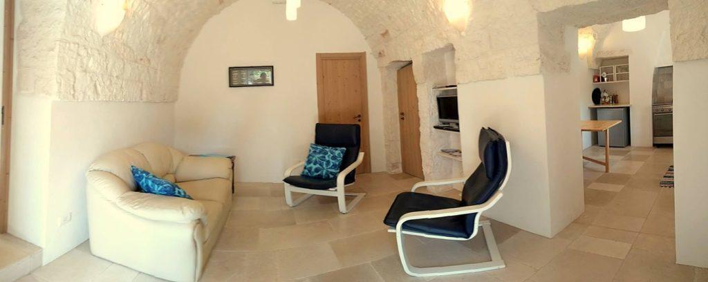 lounge stonehouse, met twee gemakkelijke leunstoelen en een bankstel. Doorkijk naar keuken.