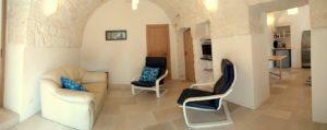 lounge met makkelijke leunstoelen in stonehouse met bank leunstoelen en doorkijkje naar de keuken