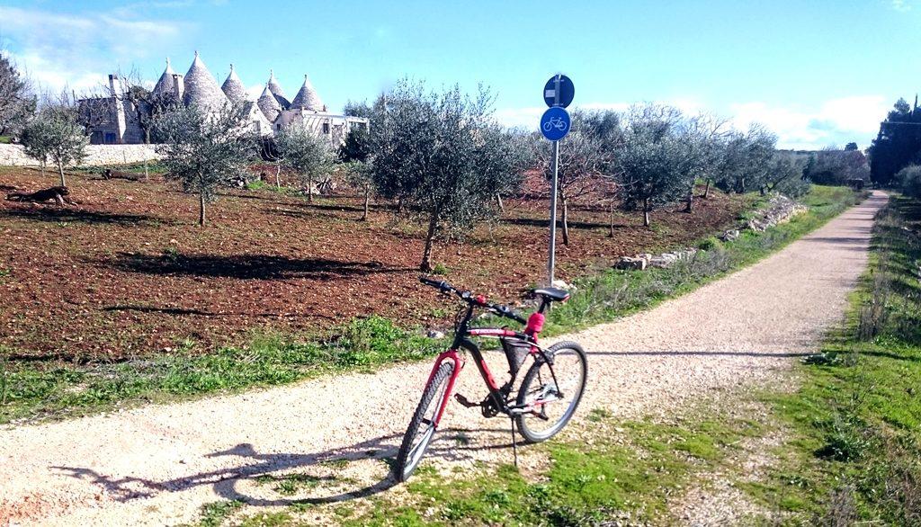 een mountainbike geparkeerd op fietsbad met op achtergrond een trullo