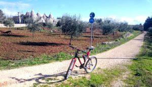 een mountainbike geparkeerd op fietspad in Puglia met op achtergrond een trullo