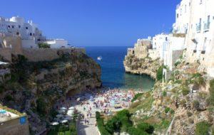 inham van polignano a mare met badende mensen in de zee en een strandje.  een van de vele dorpjes Puglia