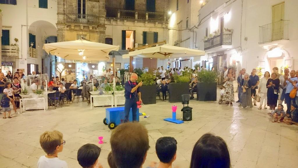 grappig gekleede artiest te midden van een cirkel mensen zorgt voor enterthainment