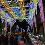 vele gekleurde lichtjes en marktkraampjes tijdens een feest met vele mensen op de been