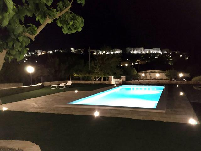 in de avond verlicht zwembad tegen achtergrond verlichte huisjes