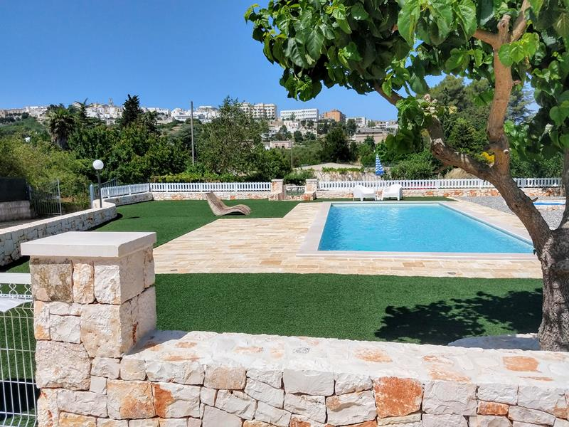 zwembad tegen achtergrond van Cisternino muurtje met een wit hekje er boven op